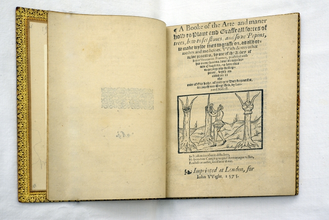 book open to the title page, the long title set in an inverted pyramid and illustrated with a woodcut of a man grafting trees