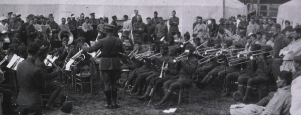 Physicians, soldiers, and patients are standing in such a way as to form a horse-shoe around the African American band members in front of a tent.