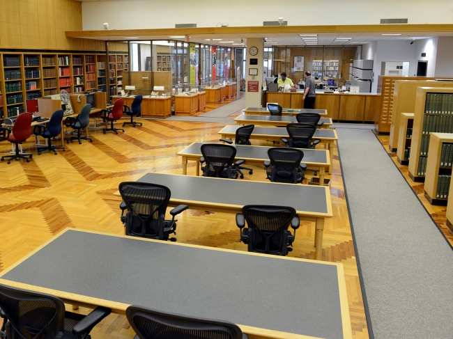 A room with decorative wood floors, tables, book shelves, display cases and an information desk.
