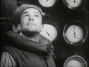 Gene Kelly, in a flotation divice stands in front of a bank of gauges looking up.