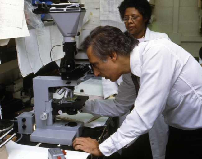 Robert Gallo looks through a microscope while a colleague looks on.