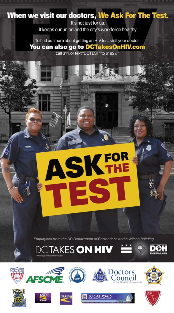 Three female officers stand holding a sign that reads Ask for the Test.