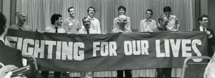 A group of men stand holding a banner that reads Fighting for our Lives