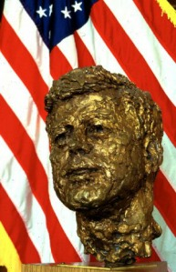 A bronze sculpture of Kennedy in front of an american flag