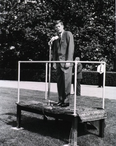 President Kennedy stands on a platform in front of a microphone