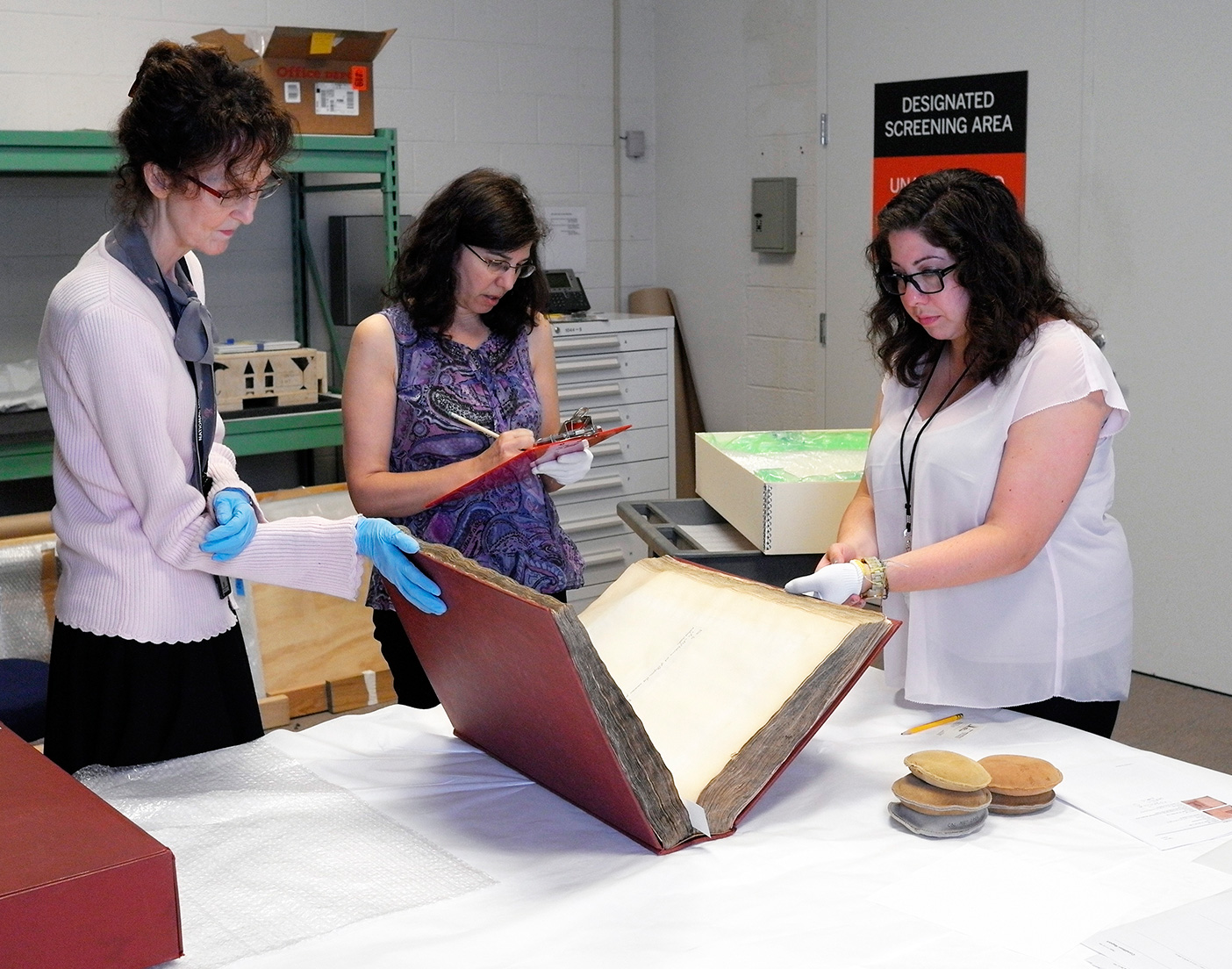 Three women examine a large book.