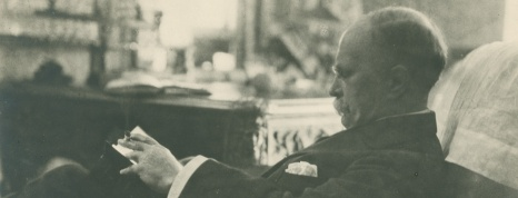 Osler reading in an easy chair.