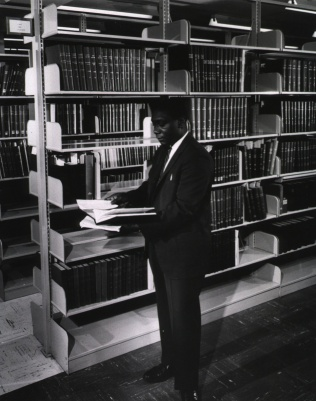 A man in a suit looks at an open book next to a library shelf.
