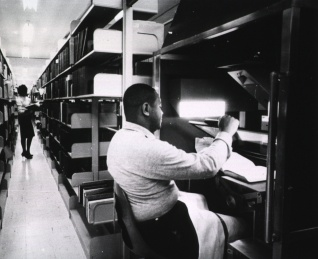 A man seated at a machine holds a glass plate over an open book.