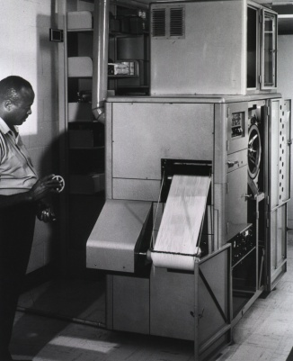 A man stands holding a mirofilm reel next to a large machine producing a long roll of printed paper.