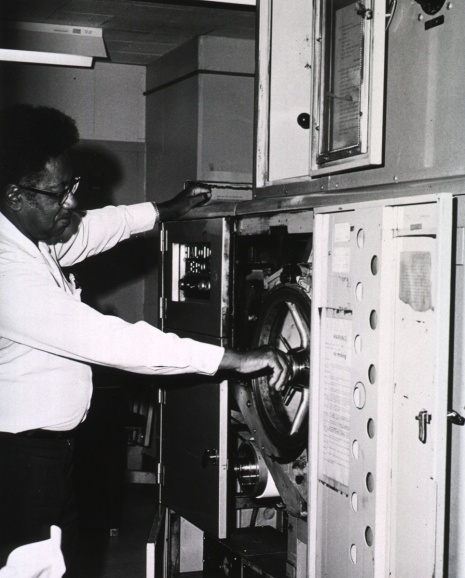A man makes a mechanical adjustment inside the cabinet of a large machineused to print from microfilm on to rolls of paper.