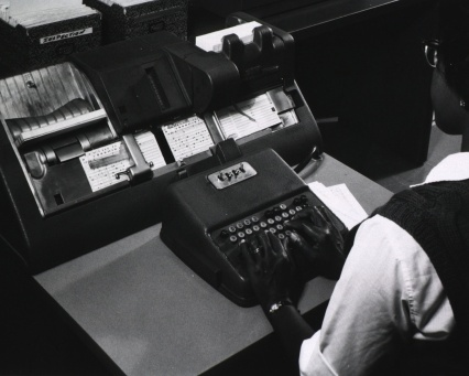 An operator types on a typewriter like keyboard while a machine creates punch cards.