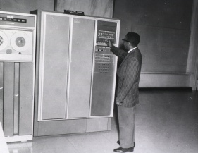 A man adjusts the settings on a cabinet sized machine.