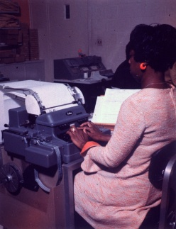 A woman types at a machine that prints a long continuous sheet of paper.