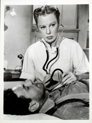 June Allyson in a nurses uniform uses a stethescope on a prone male patient.