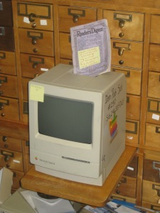 "An old Readers Digest magazine with a post it note one it on top of an old Macintosh Classic II computer tagged with another post it reading ""not working"" in front of an old card catalog."