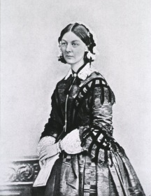 Formal portrait, standing in a fine dress, holding a folded paper.