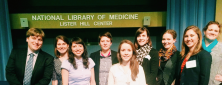 Nine young professionals pose at the Lister Hill Center at the National Library of Medicine.