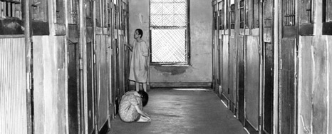 Two patients in smocks, one standing, one seated on the floor, in a hallway lined with barred metal doors.