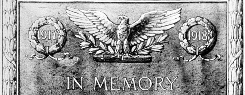 A carved stone plaque featuring an American with the dates 1917 and 1918 to either side and In Memory beneath..