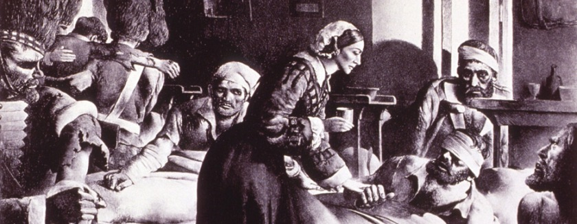 In a room filled with a chaos of bleeding and bandaged soldiers, a woman comforts a bandaged man lying on a cot.