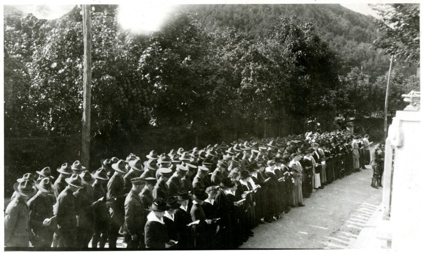 A crowd of men and women in military uniform attend an outdoor ceremony.