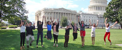 A group of people jumping in front of the US Capitol Building