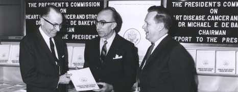Three men in suits look at a report during the President's Commission on Heart Disease Cancer and Stroke.