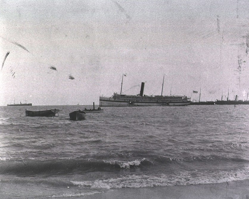 A large steam ship just offshore, flying an american flag, other boats of various size in the fore and background.