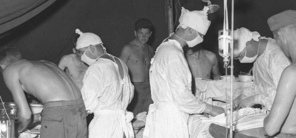 Surgeons operate under a tent while soldiers in fatigues look on.