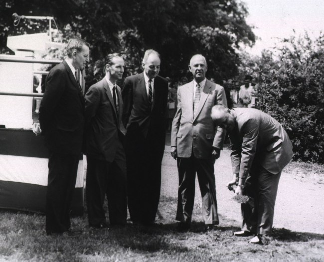 Four white men in suits stand watching a fifth shovel dirt.