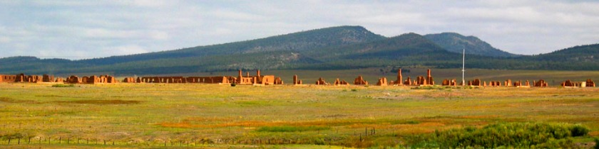 A wide landscape with low mountins in the background and the ruins of a large fort.