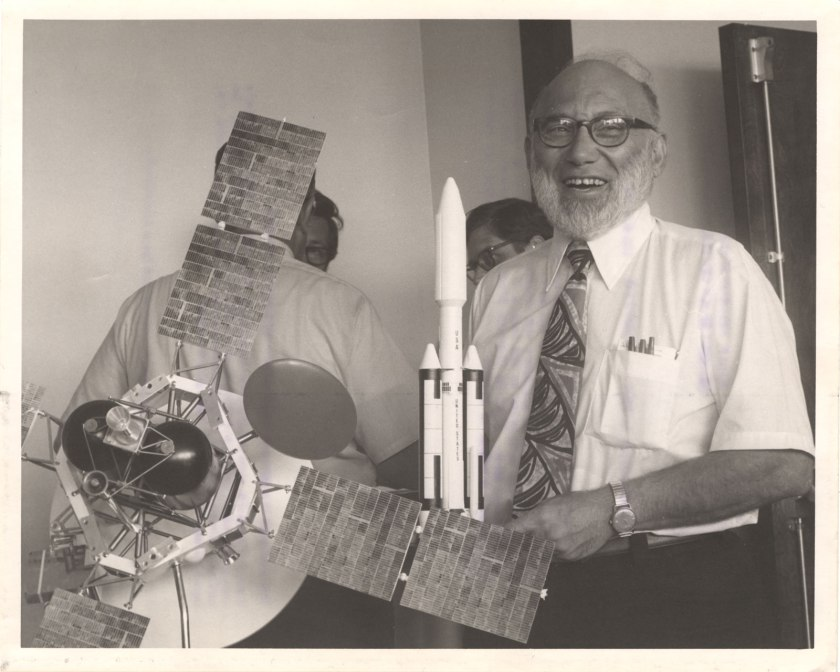 Joshua Lederberg stands with models of the Viking 1 and it's rocket.
