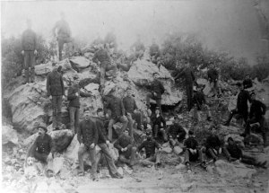 A group of about 30 soldiers in uniform stand and sit on a rock outcrop.