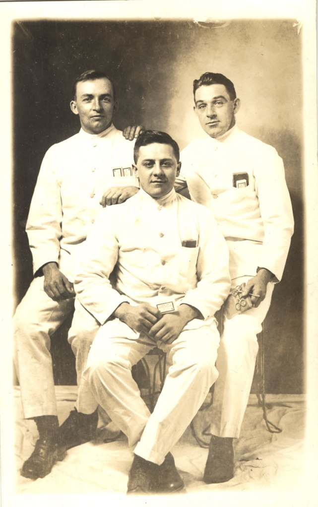 Three men in white uniforms sit together posed for the camera.