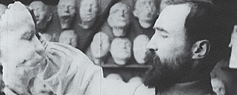 In front of a wall of masks a man holds one up, facing it in profile.