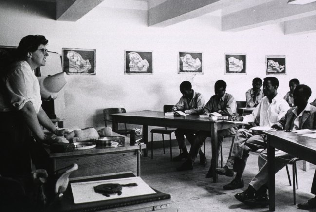 A white woman lectures to a room of young black men, a model of an infant is on the desk in front of her.