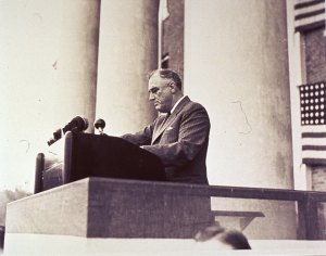 Roosavelt, in a pinstripe suit, stands at a podium flanked by columns.