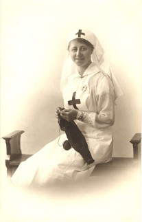 A White female nurse in white smiling, knitting, and looking at the viewer
