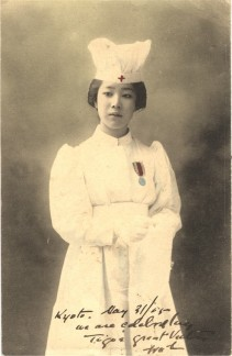 An Asian female nurse in white, wearing war medal, looking slightly off to the left.