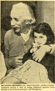 A clip from a newspaper of a photograph of Einstin holding a child on this lap.