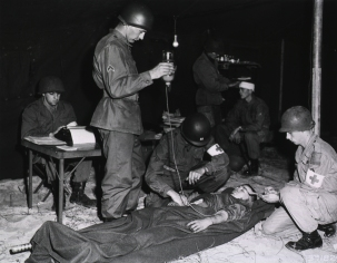 Photograph of army doctors treating a wounded soldier