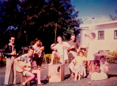 A group of young white people entertain themselves with a guitar and beverages.
