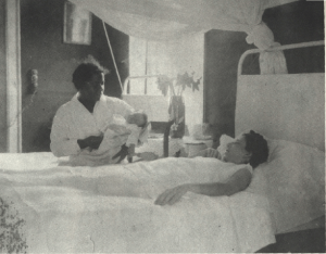 A woman holding a newborn sits by a woman lying in a bed.