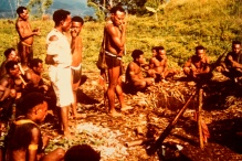 A group of Fore people sitting and standing around a pit in the ground.
