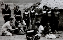 a white man uses a stethescope on a black patent seated on the ground outdoors while another withe man and a group of black men in milatary style uniforms and indigenous dress look on.