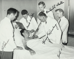 A photograph of a doctor and patient and four others. Names of all but the patient are handwritten on the photograph.