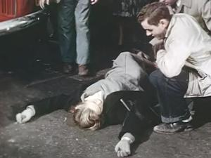 Wndy lies unconcious in the street while a group of people gather around.