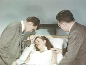 Wendy lies unconcious on a bed in a hospital, two men care for her.