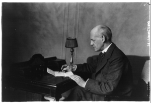 John Galsworthy seated at a writing desk reviewing a document, left profile.